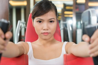 Portrait of a fit girl with intense look working out in the gym