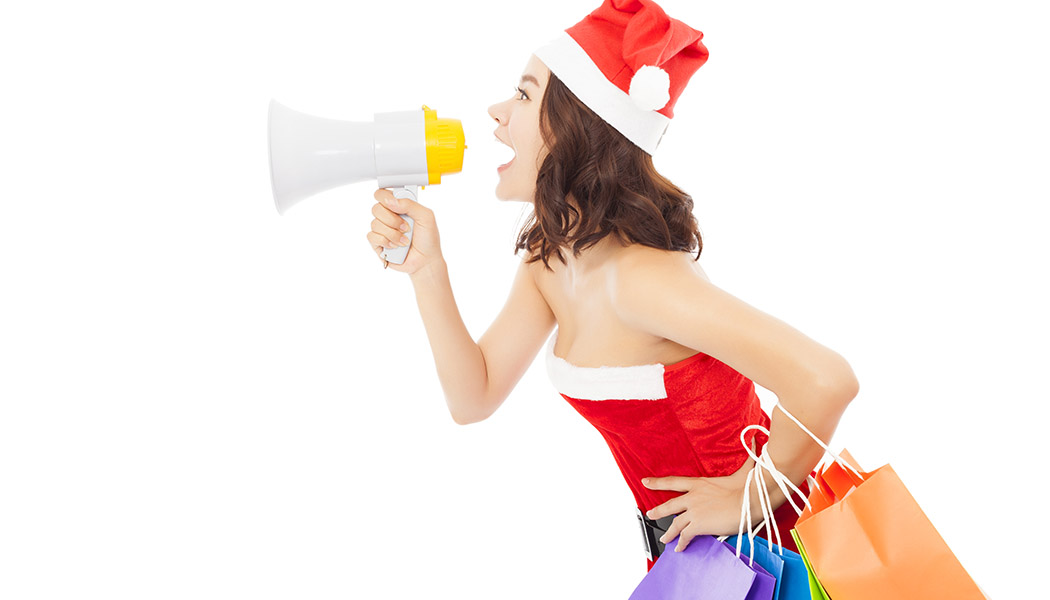 Christmas santa woman using a megaphone with gift bags